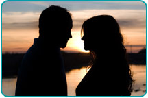 Silohuettes of two ex-lovers staring into each others' eyes at sunset, wondering if they should reignite their old flame