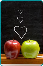 Red & green apples sitting on the chalk shelf of a schoolroom chalkboard with three cartoon hearts drawn above them on the blackboard