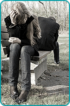 Depressed woman and man sitting on park bench
