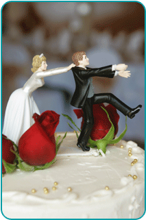 A wedding cake topper, in which the bride is holding the collar of the groom who is attempting to run away