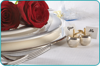 A fine dining table set for a romantic Valentine's Day dinner, complete with roses