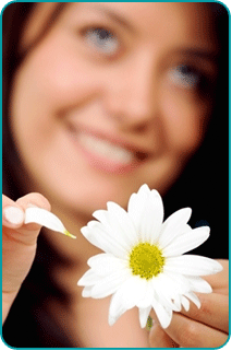 Smiling woman thinking of love opportunities as she plucks the petals from a daisy
