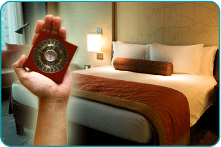 A woman's hand holding a feng shui compass, or luopan, in order to better optimize her bedroom for lovemaking