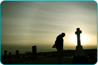A person mourning a loved one in front of a gravestone at dusk