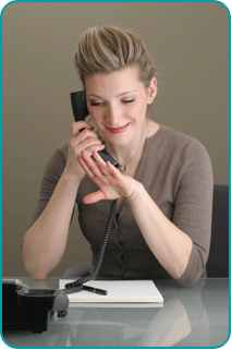 A newly-engaged woman looking at her engagement ring while talking to her psychic on the phone