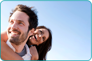 Smiling woman holding smiling man from behind with blue sky behind them
