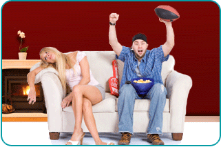 Bored woman with excited sports-fanatic man on couch in living room