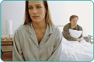 Distraught woman in pajamas at foot of bed with her dissatisfied lover clutching pillow on other end of bed