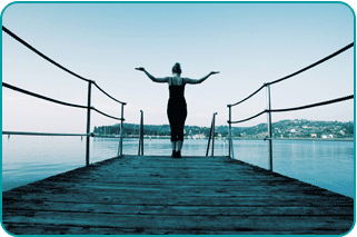 Revitalized woman holding her arms in the air at end of pier on a lake, confident in knowing she chose what's best for her