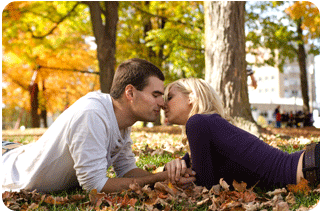 A couple lying on fallen leaves about to kiss