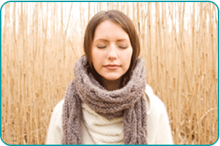 A woman meditating outside in front of dried grasses