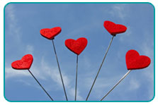 Five felt hearts on sticks over blue sky background
