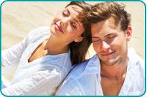 A couple meditating on the beach